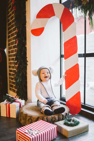 New year and Christmas holidays theme Caucasian child boy 1 year old sitting on a stump felled tree near the window in a funny hat. Scenery large red striped candy.
