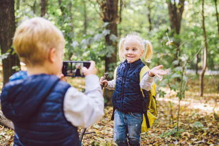 Children preschoolers Caucasian brother and sister take pictures of each other on mobile phone camera in forest park autumn. theme of hobby and active lifestyle for child. Profession photographer.
