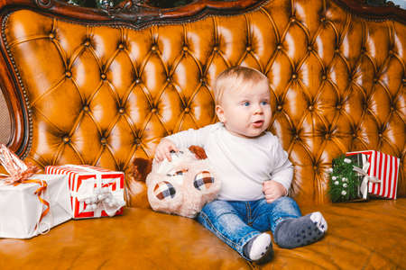 Happy little smiling boy with christmas gift box. Beautiful little baby, sits on asofa with gift. Child sitting by a pile of Christmas presents. Christmas gift concept. Banco de Imagens