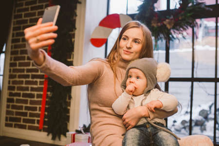 christmas, technology and family concept, happy mother and little son taking selfie by smartphone at home. Kid and mom make selfie on mobile phone. mother and child makes photo self-portrait in winter