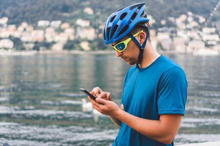 The theme of tourism and travel in Italy. A male cyclist uses a phone on the shore of Lake Como. Tourist guy in a helmet with a bicycle on the shore of a mountain lake in northern Italy.