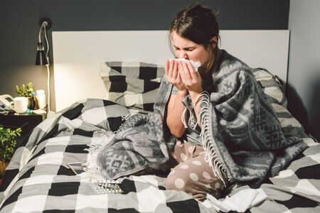 sick woman with runny nose, sitting in bed. woman feeling unwell and sneeze bedroom. Woman holding tissue ,flu symptoms. Healthcare medical concept. Cold And Flu Season. woman with allergy symptoms.