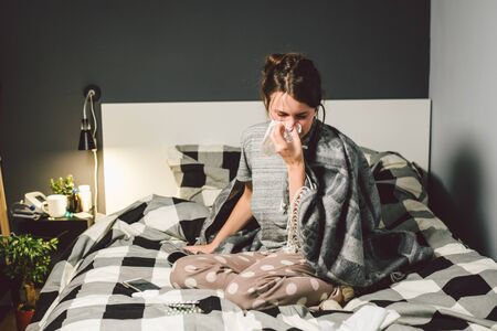 sick woman with runny nose, sitting in bed. woman feeling unwell and sneeze bedroom. Woman holding tissue ,flu symptoms. Healthcare medical concept. Cold And Flu Season. woman with allergy symptoms. 写真素材