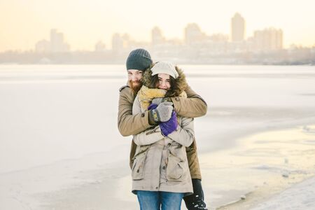 Young couple cheerfully flounders in snow. Between comic fight. Happy young couple hugs in winter snowy woods. Romantic lifestyle men and women in love. St. Valentine Day date Christmas hugging happy. Stockfoto