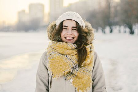 Beautiful happy laughing young woman wearing winter hat and scarf. winter background with snow. Winter holidays concept. Happy Woman In Winter Nature. Stockfoto
