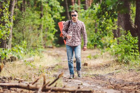 Young man walking in forest. He exploring forest, enjoy in autumn day, holding bottle in outdoor forest scenery. Adventures hiking. Outdoor lifestyle freedom concept.