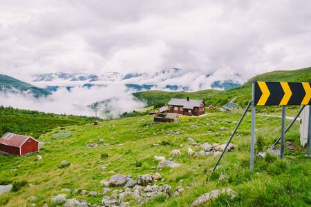 Norwegian landscape with typical scandinavian grass roof houses and the sheep grazing in the valley. Idyllic landscape of sheep farm in Norway. view rural landscape with farmhouses plateau and sheep o 스톡 콘텐츠