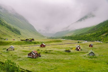 Beautiful landscape and scenery view of Norway, green scenery hills and mountain in a cloudy day. green scenery of hills and mountain partially covered with fog. Farm and cottages on a glacier river.