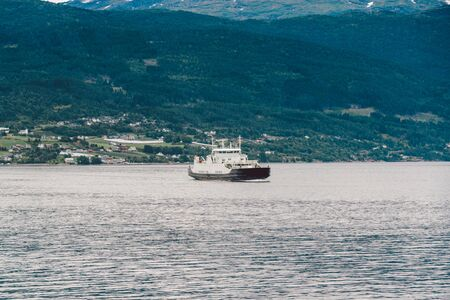 Ferry boat transportation Norway. White passenger ferry goes on fjord. In Norway. ferry crossing a fjord. Ferryboat cruising on Norwegian fjord. Imagens