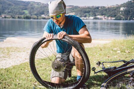 Bike Repair. Man Repairing Mountain Bike. Cyclist man in trouble rear wheel wheel case of accident. Man Fixes Bike near lake in Italy background mountains. cyclist repairing bicycle wheel outdoors.