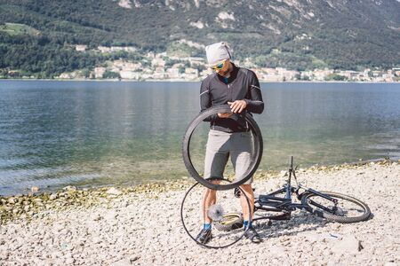 Bike Repair. Man Repairing Mountain Bike. Cyclist man in trouble rear wheel wheel case of accident. Man Fixes Bike near lake in Italy background mountains. cyclist repairing bicycle wheel outdoors.