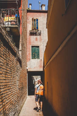 tourist with an orange backpack and bandana walks along narrow street in Europe. Italy Venice in summer. The facade of old houses without people and crowds of tourists. Unpublished places in Venice. Stock Photo