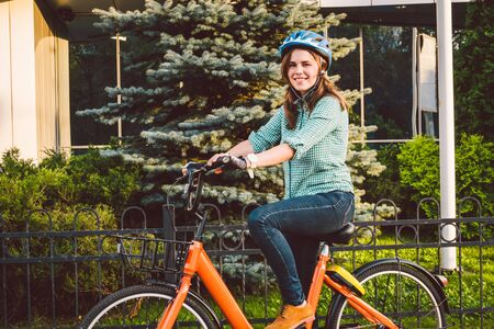 Attractive Friendly Young Woman With Her Bicycle. Portrait of young woman on the street with bicycle. ecological bicycle transport. Student girl came to study at the university on a rental bike.