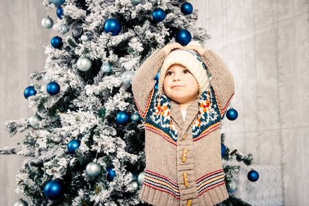 Christmas theme and children. Little Caucasian boy child in a warm hat and sweater posing, eating sweetness, dirty face. Christmas morning. New Years holidays. Фото со стока - 134712735
