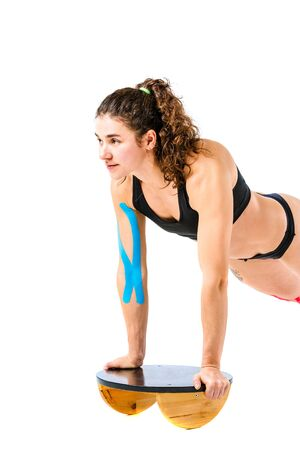 Kinesio tape girl, exercise push ups. Attractive Young sport Woman Doing Push Up Exercise in full length isolated on white background. Theme kinesiology tape rehabilitation and health of athletes.