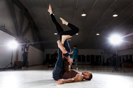 Couple does acroyoga, physical practice yoga and acrobatics. Balance and concentration couple. Men and woman, pair acroyoga flexibility workout. Fit active pair yoga time. Meditation, yoga, asanas. Stock Photo