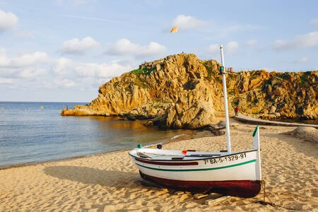 traditional old wooden fishing boat on the rocky beach. Travel concept. Costa Brava, Spain. Fishing boat rest on golden sand beach overlooking the blue sea. Wooden Fishing Boat Spain.