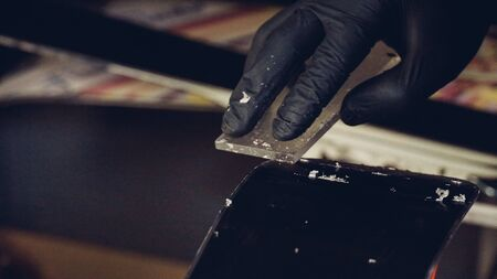 Ski maintenence. Removing excess wax from race ski base plastic scraper. Ski service and repair. Winter shop worker doing base repair. Rental workshop service. Repairman In Workshop Ski Service.