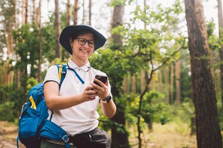 Girl tourist use smartphone on hike, looks maps and navigation. Woman with backpack using smart phone on beautiful nature.Travel concept. Outdoor travel. Travel and explore. Female Tourist Using gps.