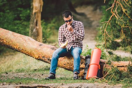 Eating banana Outdoors Hiking Trail. theme hiking and nature travel. Tourist take a rest and eating babanas. picnic in the forest. tourist eat snack food. Vitamin charge.