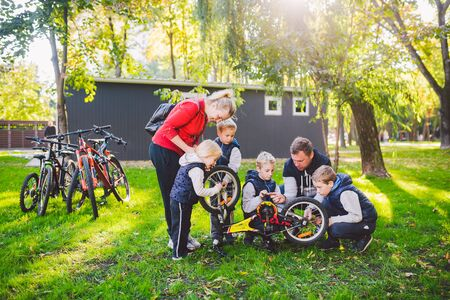 The theme of teamwork and friendly family. Outdoor activities. Parents teach children how to solve problems. Father shows how to repair a bike by himself. Repairing a childrens bike in a park.