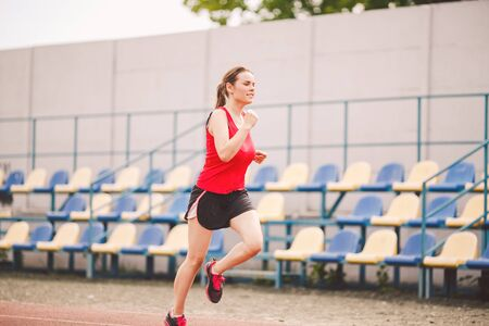 Woman Running At The Stadium. Young woman running during on stadium track. Goal achievement concept. Fitness Jogging Workout on ballpark. Wellness theme. Sporty training cardio for weight loss success