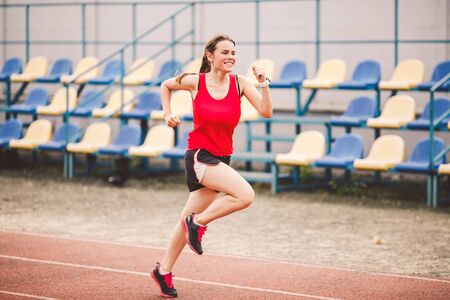 Female runner jogging on stadium track, woman athlete running and working out outdoors, sport and fitness concept. Young woman in sportswear training on a stadium. Sport lifestyle topic.