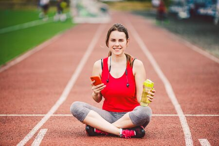beautiful fitness girl uses smartphone at stadium after workout. Sports and healthy. Sport woman use of cellphone inside sport complex. Sport and technology. resting after workout, run at red track.