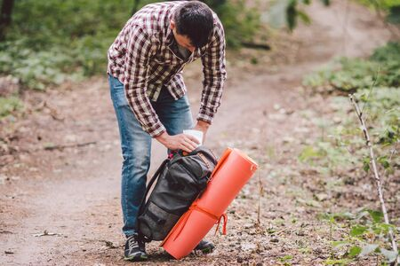 Hiker holding his camping backpack. traveler opening backpack while traveling in beautiful wood. Theme hiking and travel. Man traveling in forest with backpack. Active healthy man hiking in forest.
