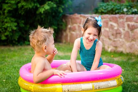 Two little brother and sister playing and splashing in pool on hot summer day. Children swimming in kid pool. Two cheerful cute children playing and having fun, splash in inflatable pool at backyard.