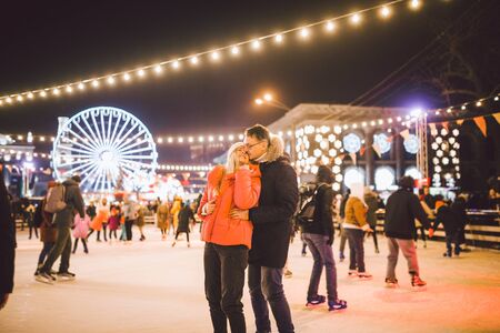 Couple in Love. Romantic Characters for Feast of Saint Valentine. True love. Happy Couple Having Fun at city ice rink in the evening. Happy romantic young couple enjoying together in skating-rink. Zdjęcie Seryjne