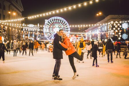 couple hugging in Saint Valentines Day. Young romantic pair having fun outdoors in winter. St. Valentines Day at city ice rink. New Year holidays. active date ice skating on ice arena on Christmas. Imagens