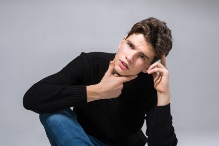 Stylish guy posing in studio sitting on the floor in denim pants and black sweatshirt. Male student portrait full on white background. Studio shot Handsome attractive european man sitting on floor.