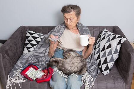 Elderly woman taking pill at home. Senior woman with her medicine tablet. ll elderly patient holding medicament pills in hands. Medicine and healthcare concept. Pharmacy, care solitude concept.