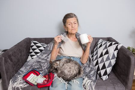 Elderly woman with pills at home. senior woman holding glass of water and pills. Granny holds pills and a cat in her arms sitting on a sofa. Age, medicine, health care, and people concept.