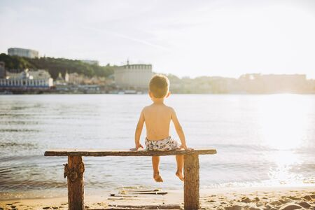 boy child sitting on a wooden bench with his back on the beach near the water and showing his hand forward direction against the backdrop of the city of Kiev.