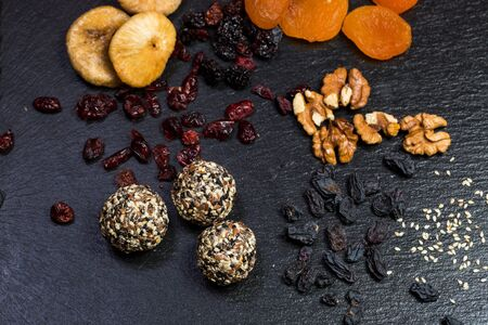 Theme sweet dessert made from natural products without sugar. Macro close-up of deserts ball round candy truffle on a black plate with natural dried fruit and seeds of white and black sesame and flax.