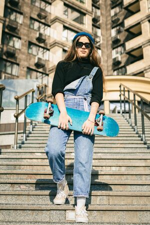Stylishly dressed woman in blue denim jumpsuit posing with skateboard. Street photo. Portrait of girl holding skateboard. Lifestyle, youth concept. Leisure, hobby and skate in the city. Foto de archivo