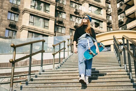 Urban woman with skate. Hipster girl with skateboard in city. Extreme sport and emotions concept. Alternative lifestyle. Stylish hipster girl holding skateboard and posing. Street style outfit. Foto de archivo