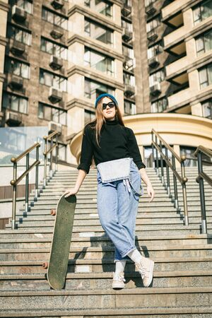 Young caucasian woman posing on street with skateboard in hands. Teenager girl in blue jeans extreme sports in an urban environment. Theme of youth recreation, lifestyle. Skateboarder in the city.