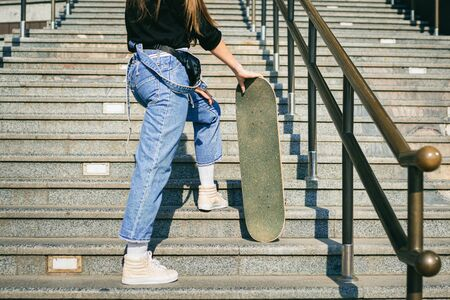 Urban woman with skate. Hipster girl with skateboard in city. Extreme sport and emotions concept. Alternative lifestyle. Stylish hipster girl holding skateboard and posing. Street style outfit.