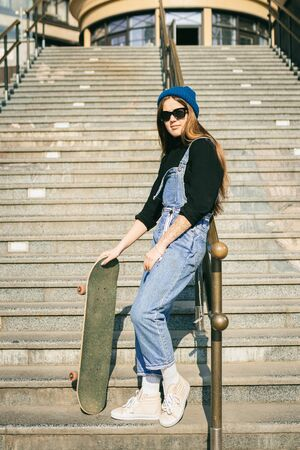 Stylishly dressed woman in blue denim jumpsuit posing with skateboard. Street photo. Portrait of girl holding skateboard. Lifestyle, youth concept. Leisure, hobby and skate in the city.