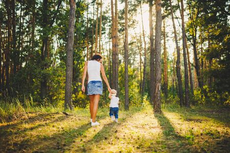 beautiful and stylish mother leads the hand of a girl of one year from birth in the park against the background of tall coniferous trees. Family values mom learns to walk a child