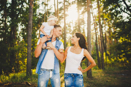 stylish young Family of mom, dad and daughter one year old blonde sitting near father on shoulders, outdoors outside the city in a park amid trees in summer. Wear jeans clothes. Family photo session