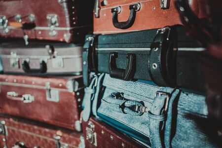 stack of old suitcases that have seen a lot of traveling. retro luggage. Lots of vintage leather suitcases.