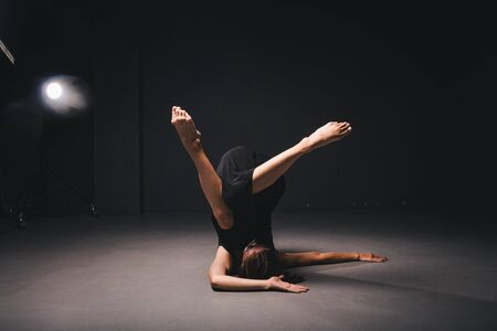 Portrait of a beautiful woman dancing on black background. Ballet and contemporary dancer dancing on dark backdrop. Contemporary Art. Plastic and flexible girl in black clothes posing on a black wall.
