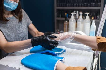 Spa Salon. Manicure. Paraffin Hand Bath. process paraffin treatment. Bowl, additive. Wax bathtub Care. Nail care. Nail artist doing manicure. Professional master putting mitten on hand customer. 免版税图像