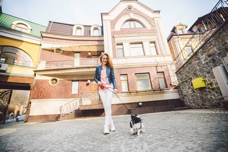 Woman walking with dog in city street. young redhaired Caucasian woman walking along European street with small Chihuahua breed dog of two colors on leash. exercise walking with Chihuahua.