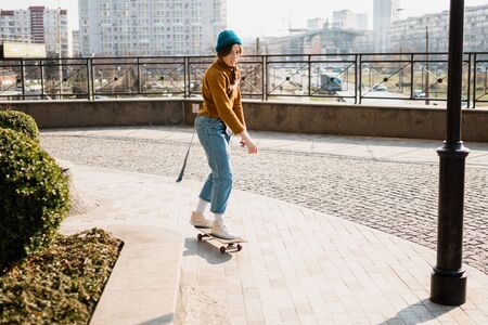 Skateboarding Woman In The City. Skater girl in denim is riding her board on the square. Athletic Woman skateboarder. Building on the background. Concept of leisure activity, urban and sport.