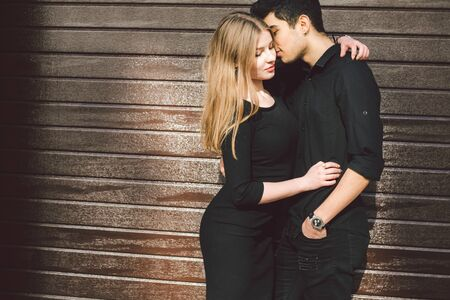 Multiracial stylish couple in black clothes posing on a background of a wooden wall. Turkish guy and caucasian woman date and love. Lifestyle Stylish couple of lovers. Young And Free.